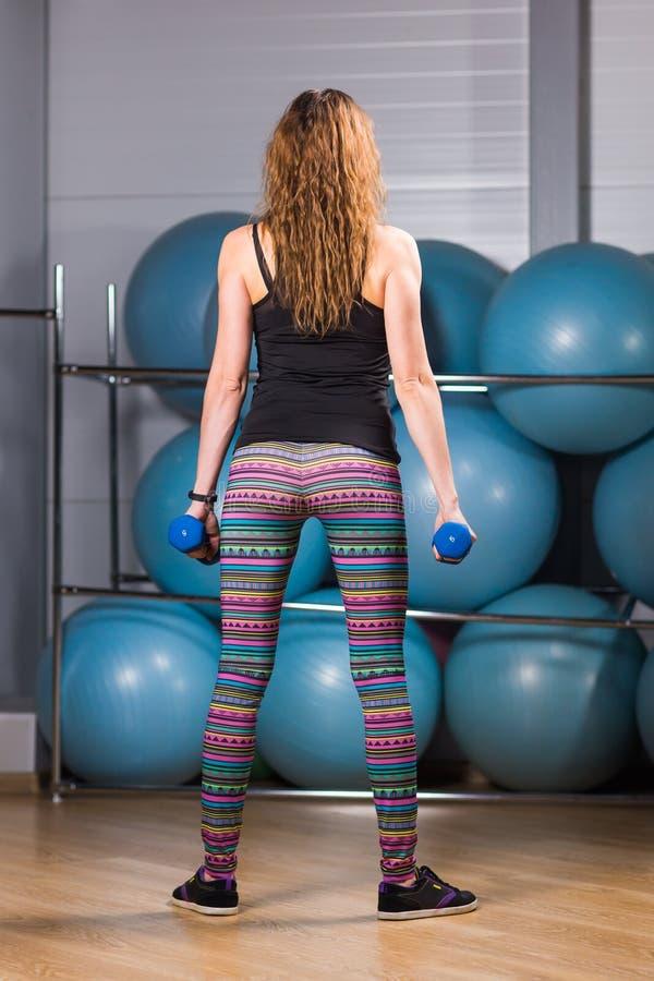 El doblar trasero muscular femenino del ` s del culturista fotos de archivo