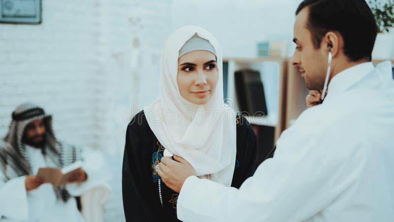El doctor árabe Checking Heartbeat una mujer musulmán imagenes de archivo