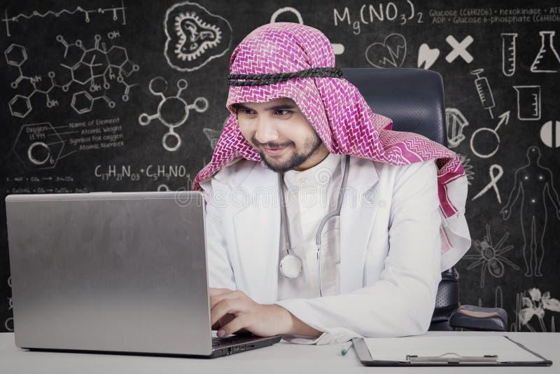 El doctor árabe utiliza el ordenador portátil en laboratorio foto de archivo libre de regalías