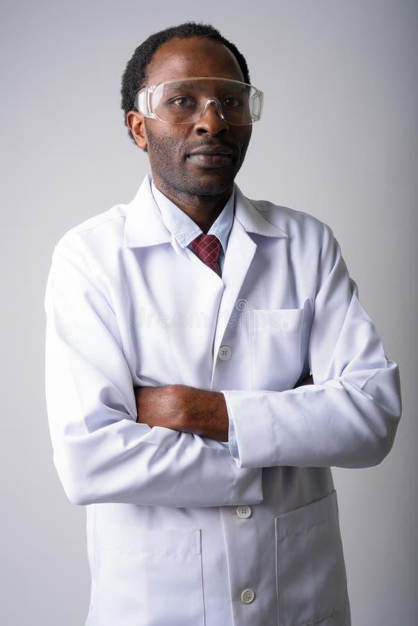 El doctor africano del hombre que llevaba los vidrios protectores con los brazos cruzó imagen de archivo libre de regalías