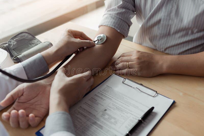 El doctor asiático está utilizando el estetoscopio para tocar el brazo del paciente fotos de archivo