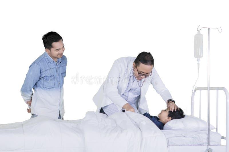 El doctor asiático examina a su poco paciente en estudio imagenes de archivo