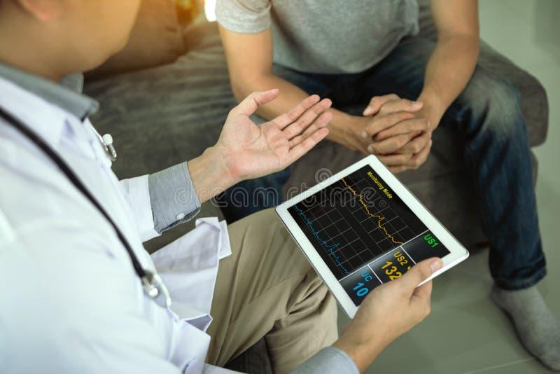 El doctor asiático visitó al paciente en casa mientras que usando la tableta que explicaba la condición paciente y el resultado d imagenes de archivo