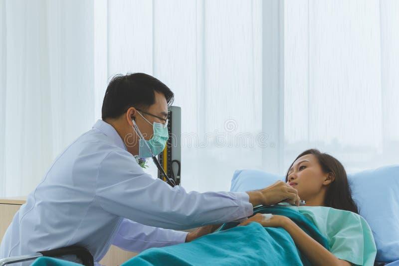 El doctor asi?tico comprueba la enfermedad del paciente femenino El doctor asi?tico comprueba la enfermedad del paciente femenino fotografía de archivo libre de regalías