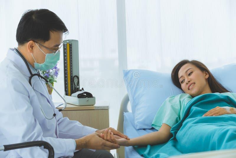 El doctor asi?tico comprueba la enfermedad del paciente femenino foto de archivo