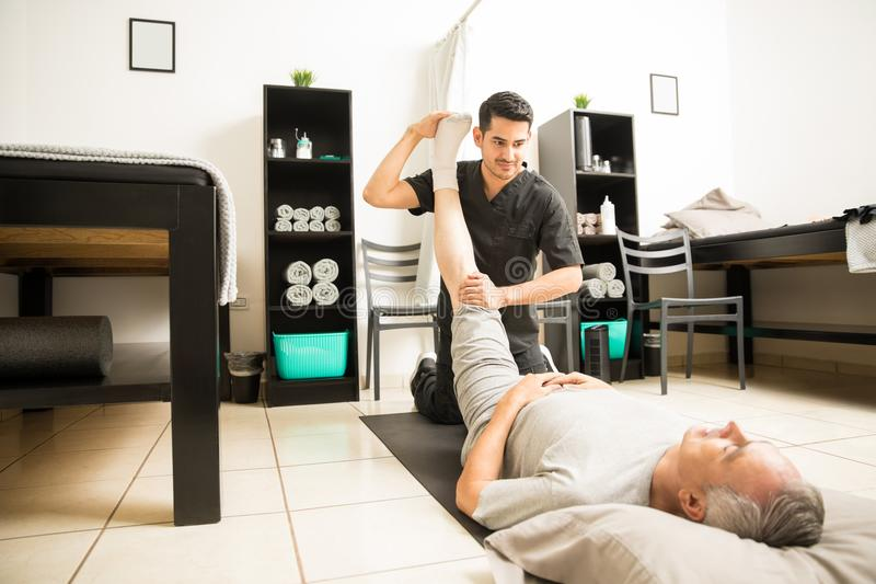 El doctor Assisting Elderly Patient con ejercicio de pierna en clínica foto de archivo libre de regalías