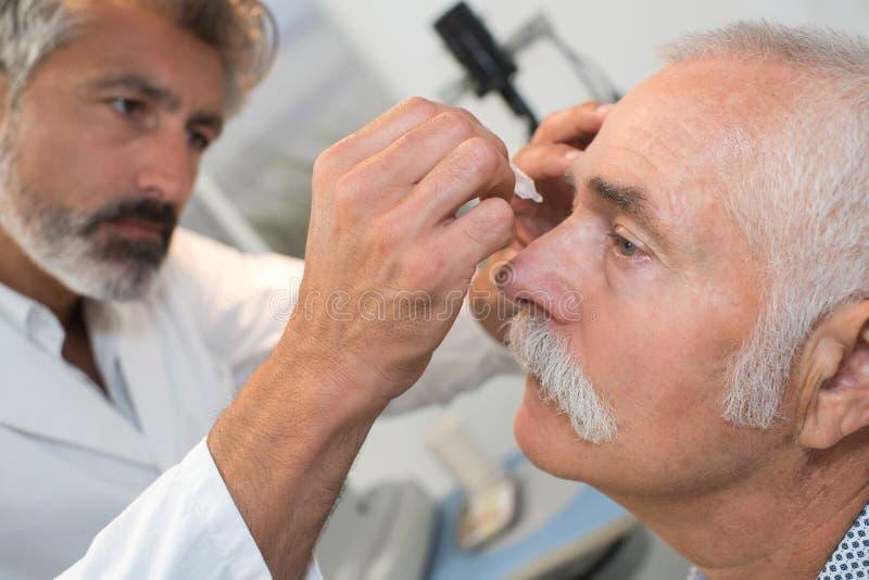 El doctor ayuda al paciente y da descensos de ojo fotografía de archivo