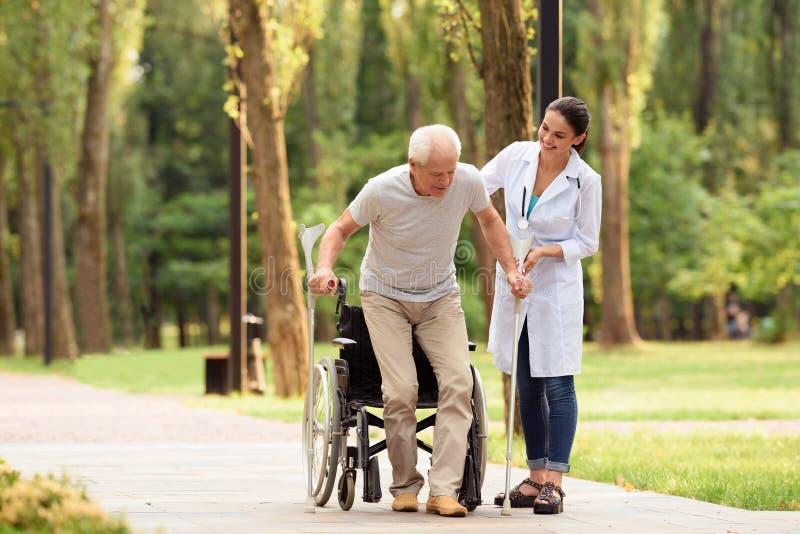 El doctor ayuda a un paciente envejecido a conseguir en sus pies imágenes de archivo libres de regalías