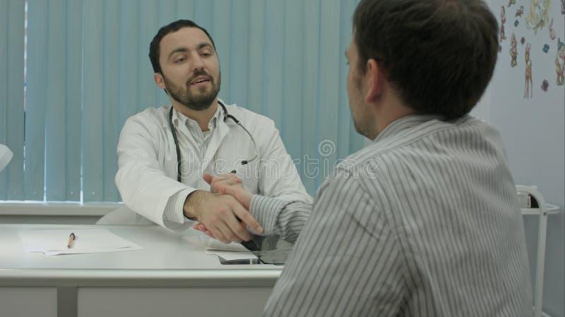 El doctor barbudo de sexo masculino en clínica con el paciente masculino sacude las manos fotografía de archivo