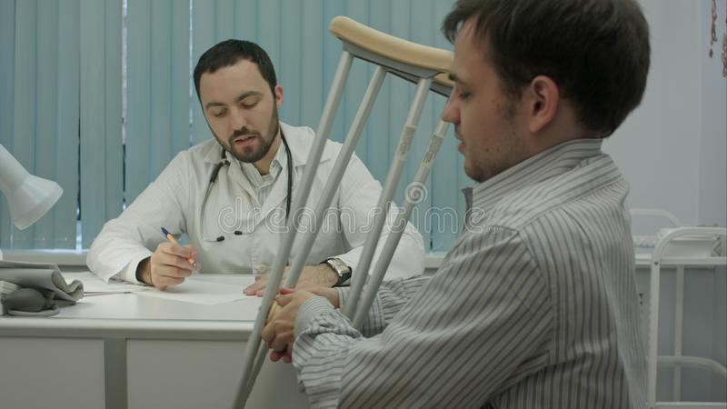 El doctor barbudo de sexo masculino en clínica consulta al cliente enfermo con las muletas imagenes de archivo