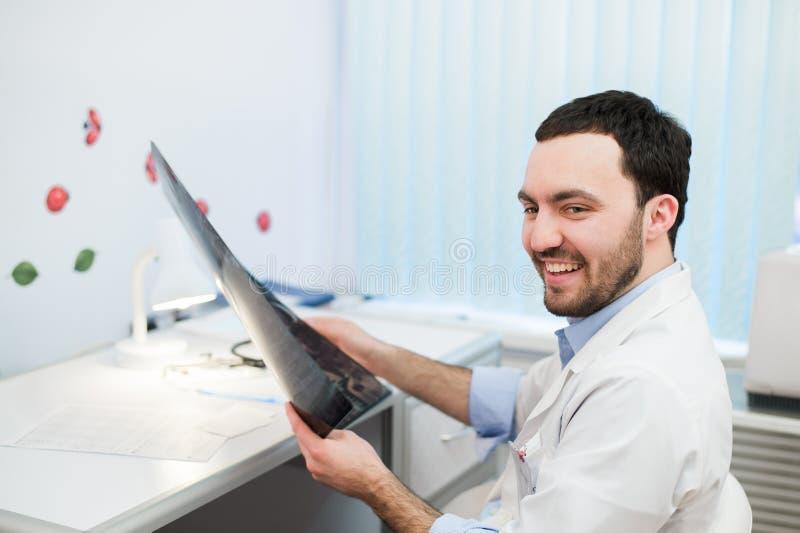 El doctor caucásico joven del hombre examina imagen de MRI de la cabeza humana en la oficina que mira el paciente y la sonrisa foto de archivo