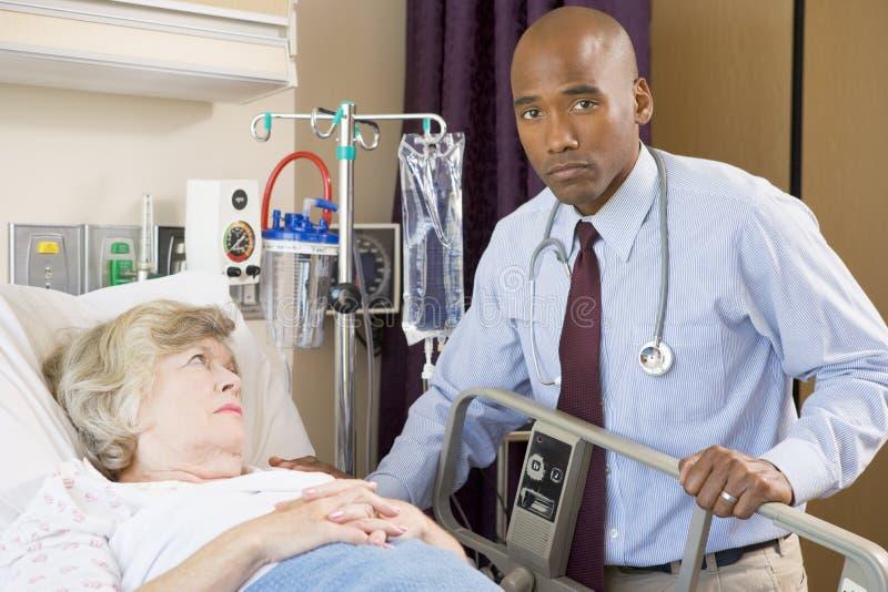 El doctor Checking Up On Patient, pareciendo serio imagen de archivo libre de regalías
