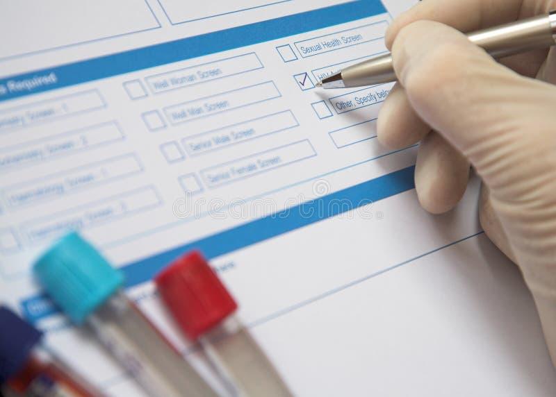 El doctor Completing una forma del análisis de sangre fotografía de archivo