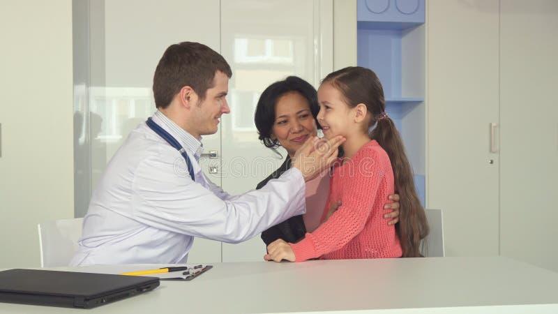 El doctor comprueba encima de niña en la oficina imagen de archivo