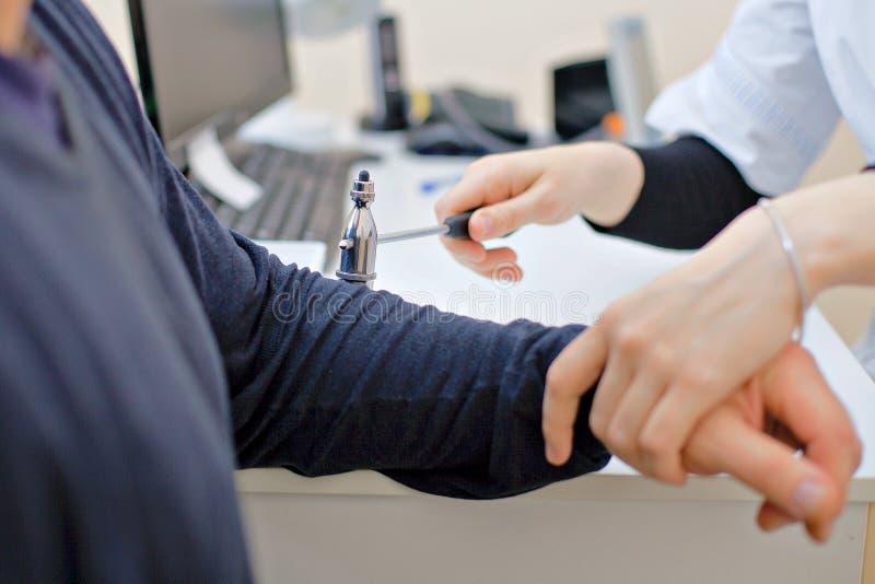 El doctor comprueba los nervios en el codo del paciente foto de archivo libre de regalías