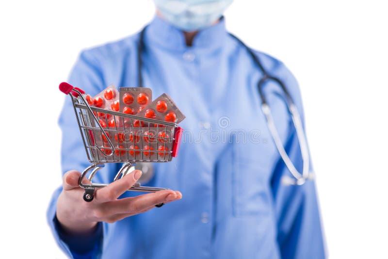 El doctor con el carro de la compra lleno de píldoras aisladas en blanco fotos de archivo libres de regalías