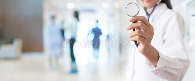 El doctor con el estetoscopio a disposición y los pacientes vienen al fondo del hospital imagen de archivo libre de regalías