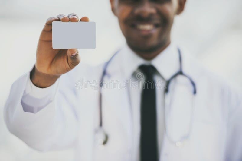 El doctor con el estetoscopio sostiene la tarjeta en hospital imagen de archivo libre de regalías