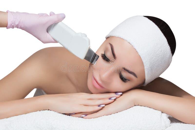El doctor-cosmetologist hace el aparato un procedimiento de la limpieza del ultrasonido de la piel facial de una mujer joven herm foto de archivo