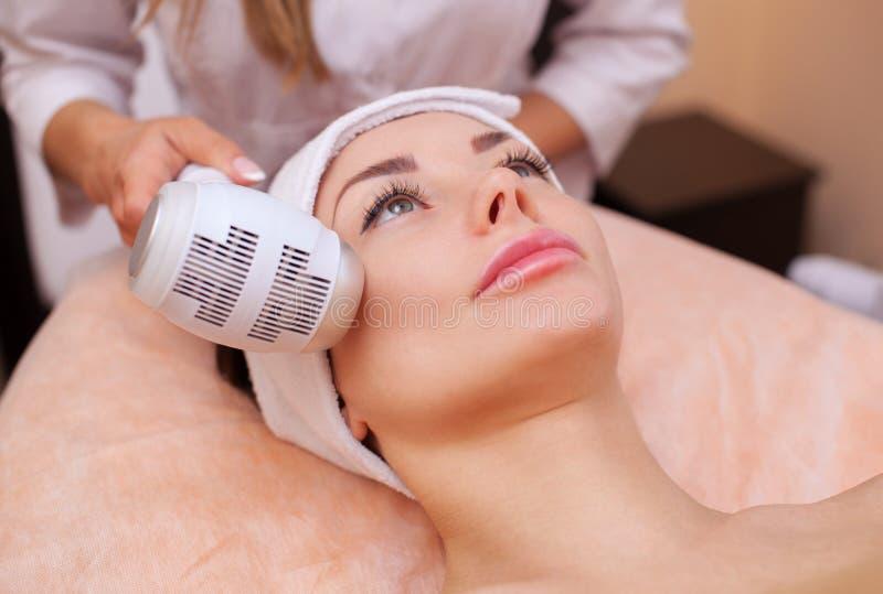El doctor-cosmetologist hace el procedimiento Cryotherapy de la piel facial de una mujer hermosa, joven en un salón de belleza imagen de archivo libre de regalías