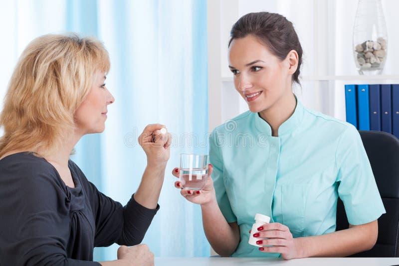 El doctor da las drogas y el agua al paciente fotos de archivo