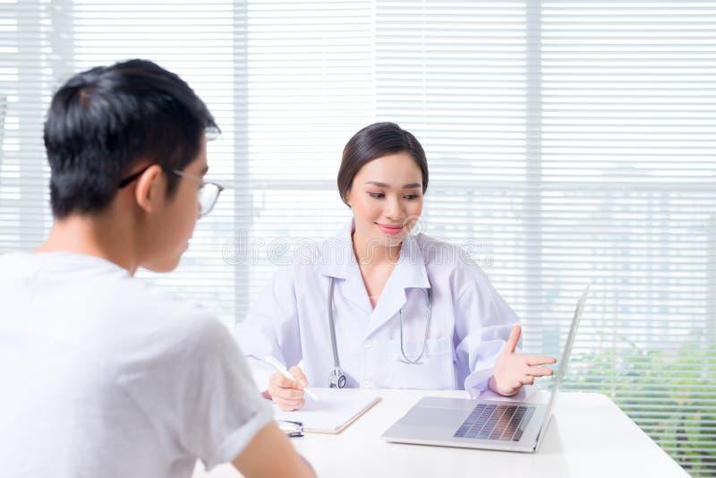 El doctor de sexo femenino amistoso da llevar a cabo la mano paciente que se sienta en fotografía de archivo