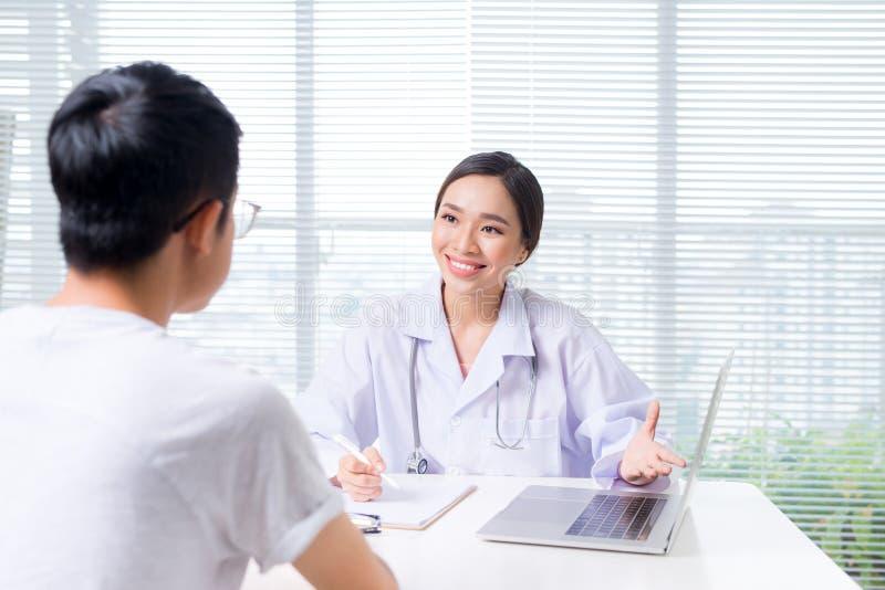 El doctor de sexo femenino amistoso da llevar a cabo la mano paciente que se sienta en foto de archivo