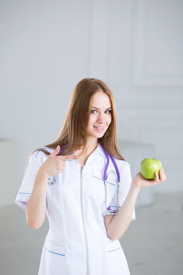 El doctor de sexo femenino es nutricionista con la manzana verde fotografía de archivo