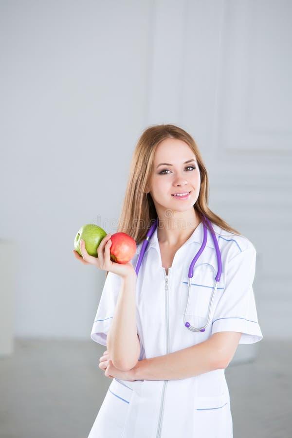 El doctor de sexo femenino es nutricionista con las manzanas fotos de archivo libres de regalías