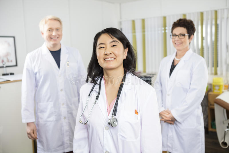 El doctor de sexo femenino feliz Standing With Colleagues fotografía de archivo