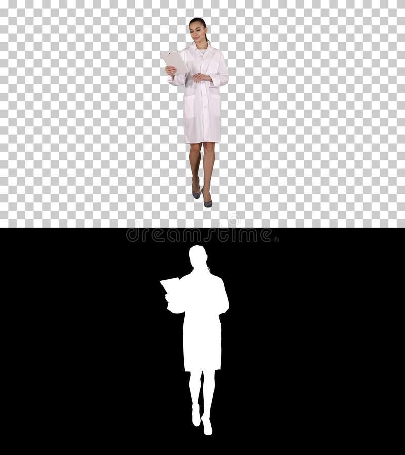 El doctor de sexo femenino feliz usando las páginas de torneado de la tableta en él, Alpha Channel imagenes de archivo