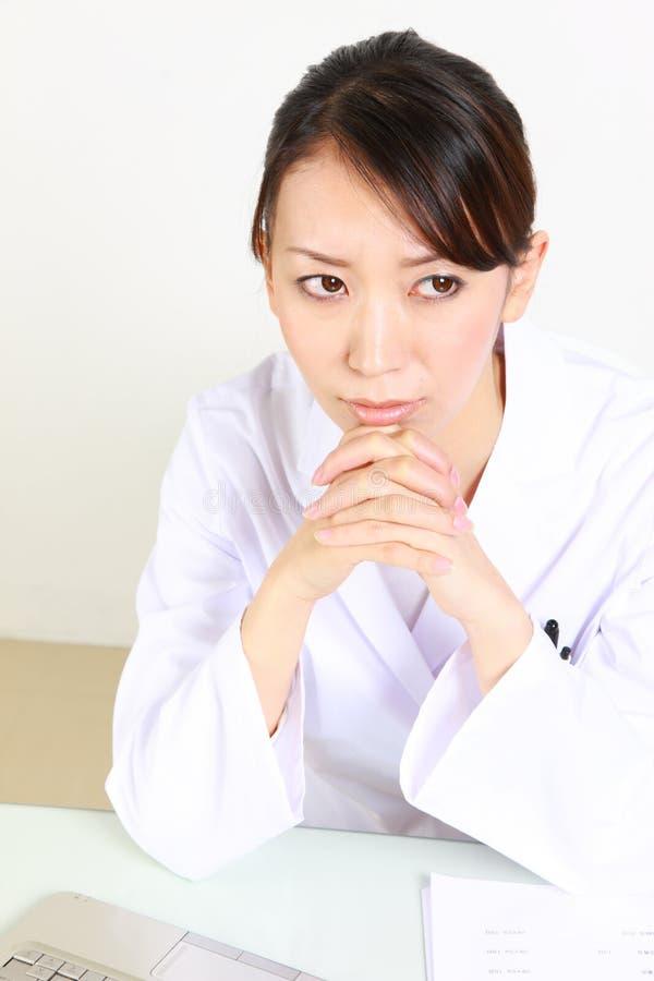 El doctor de sexo femenino japonés joven se preocupa algo fotos de archivo libres de regalías