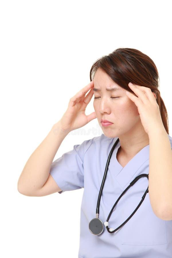 El doctor de sexo femenino japonés sufre de dolor de cabeza imagen de archivo