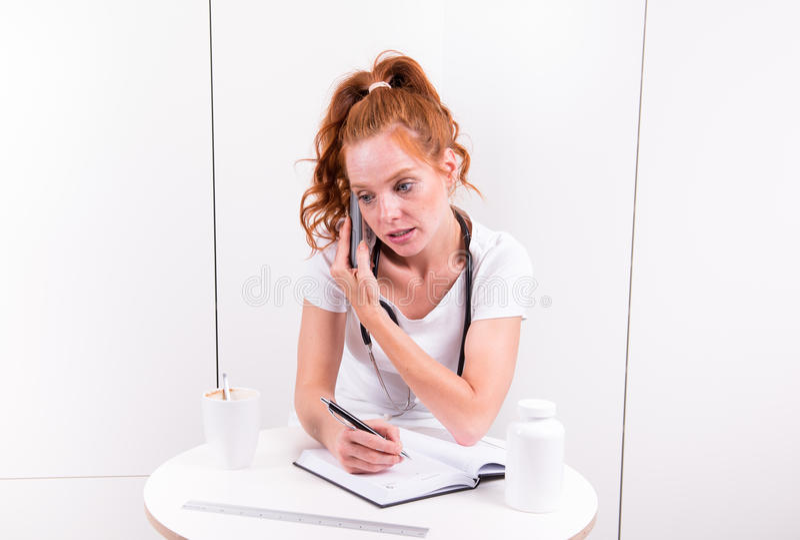 El doctor de sexo femenino joven está tomando notas durante una llamada de teléfono imagen de archivo