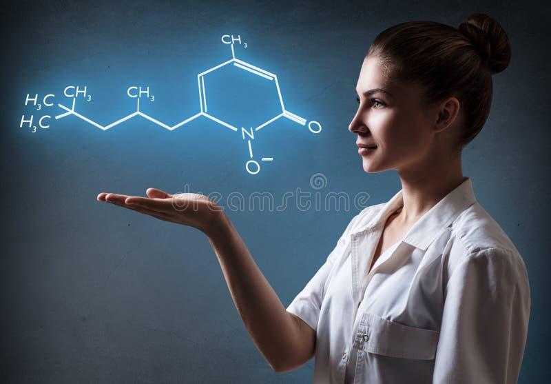 El doctor de sexo femenino joven presenta fórmula química imagenes de archivo
