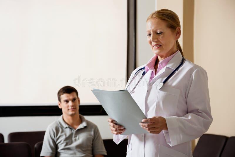 El doctor de sexo femenino Looking At File foto de archivo