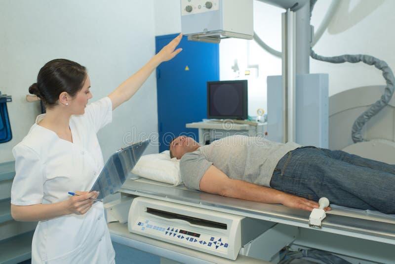 El doctor de sexo femenino Looking At Patient que experimenta la exploración del CT foto de archivo