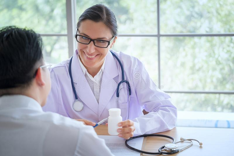 El doctor de sexo femenino mayor consulta al paciente joven que se sienta en el doctor de foto de archivo
