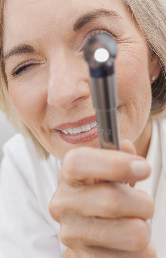 El doctor de sexo femenino mayor With Otoscope o espéculo del oído imagenes de archivo