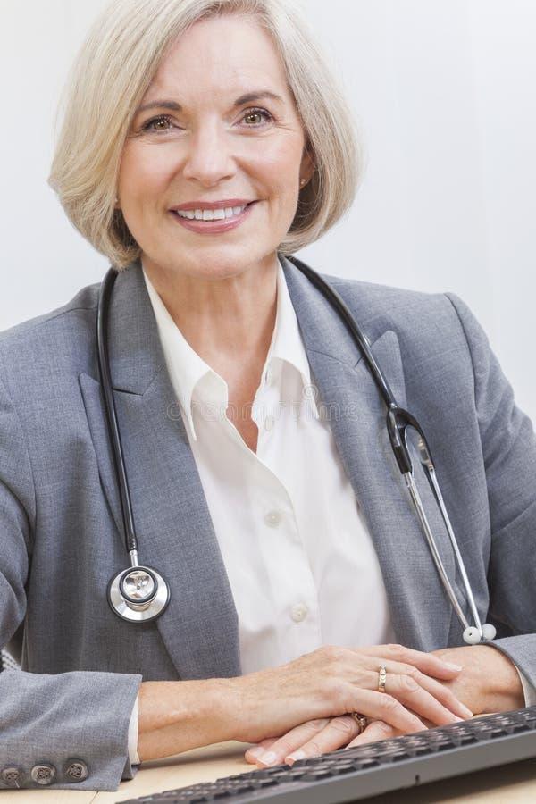 El doctor de sexo femenino mayor With Stethoscope en el escritorio y el ordenador foto de archivo