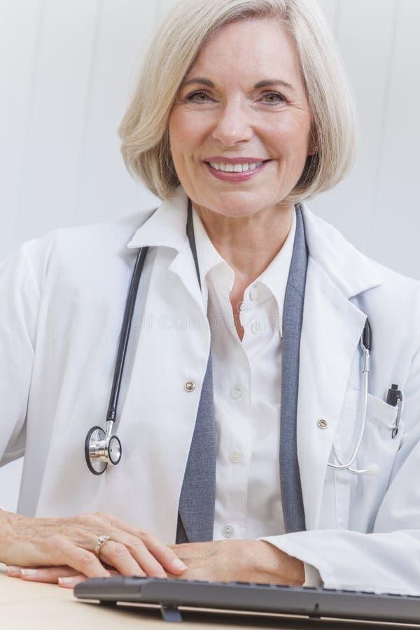 El doctor de sexo femenino mayor With Stethoscope en el escritorio y el ordenador fotografía de archivo