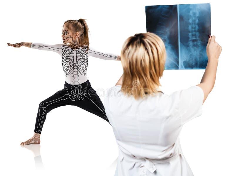 El doctor de sexo femenino mira en la radiografía de la niña en actitud de la yoga fotografía de archivo
