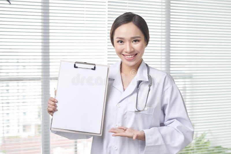 El doctor de sexo femenino muestra con el tablero fotos de archivo