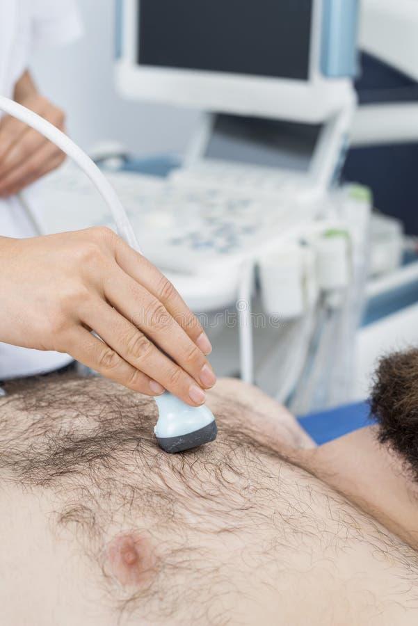 El doctor de sexo femenino Placing Ultrasound Probe en pecho paciente del ` s fotos de archivo libres de regalías