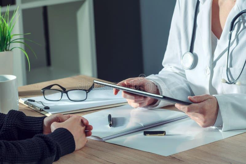 El doctor de sexo femenino que presenta el examen médico resulta al paciente que usa t imagen de archivo libre de regalías