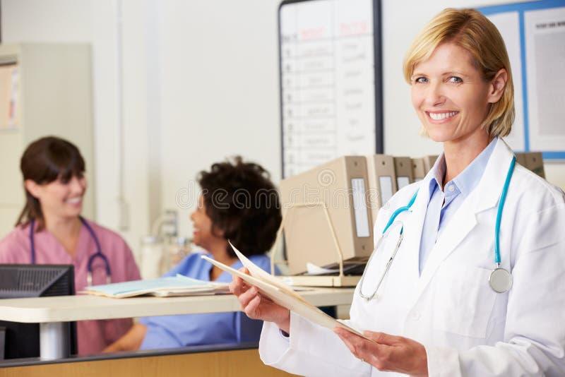 El doctor de sexo femenino Reading Patient Notes At cuida la estación fotografía de archivo