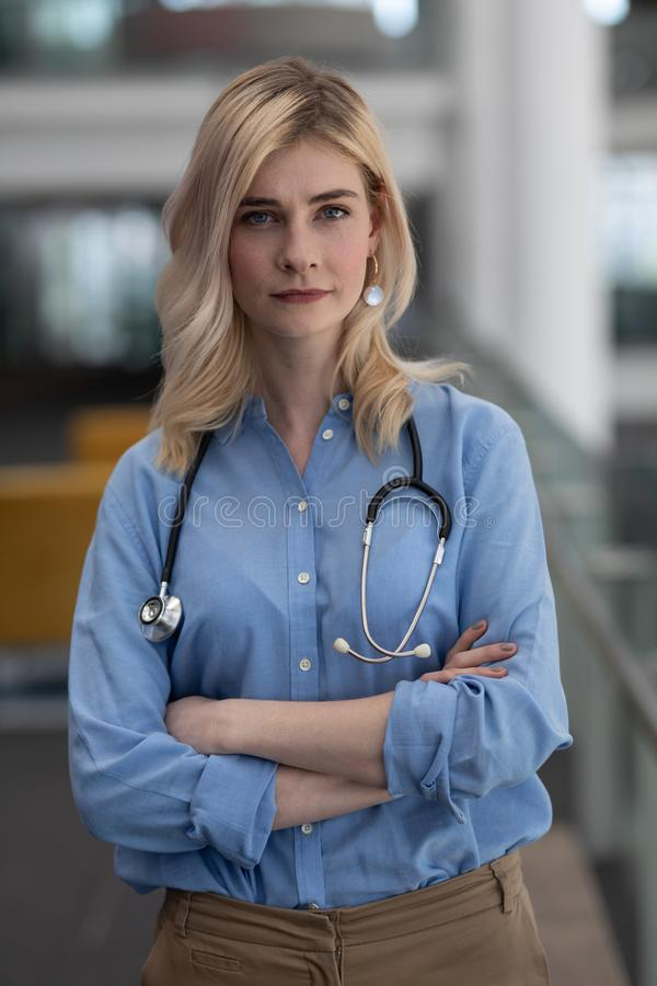 El doctor de sexo femenino rubio con los brazos cruzó la mirada de la cámara en clínica fotografía de archivo libre de regalías