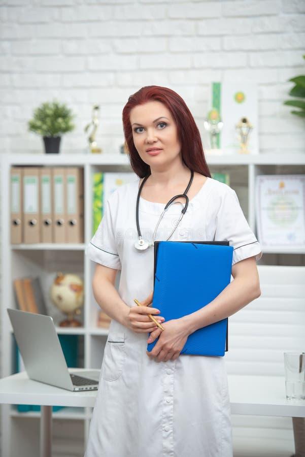 El doctor de sexo femenino sonriente en uniforme con un estetoscopio y una carpeta azul en sus manos se está colocando en su ofic imagen de archivo libre de regalías