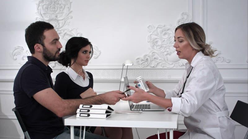 El doctor de sexo femenino vende las píldoras a los pares de la familia en la oficina fotografía de archivo libre de regalías