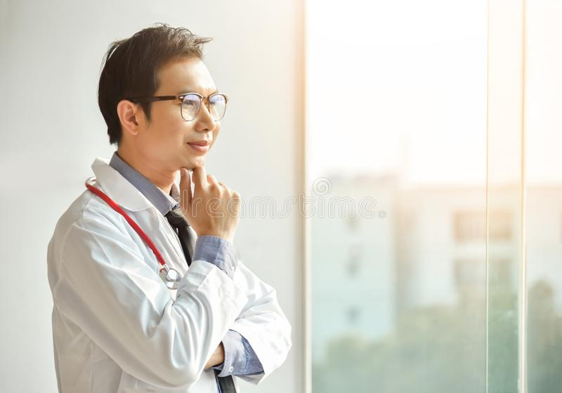 El doctor de sexo masculino asiático está presentando con los brazos cruzados fotos de archivo